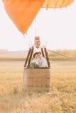 Nouveaux mariés heureux dans le panier de l'airballoon Le marié étreint le dos de jeune mariée La composition en champ Photo libre de droits