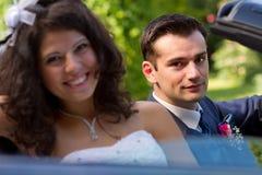 Nouveaux mariés heureux dans un cabrio Photo libre de droits