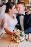 Nouveaux mariés heureux embrassant et rêvant de leur nouvelle vie mariée dans le hall de restaurant à la table Photographie stock libre de droits