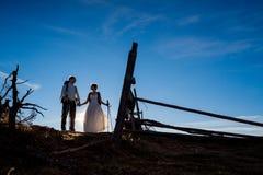 Nouveaux mariés heureux marchant avec l'équipement de montagne sur la campagne alpine Photo libre de droits