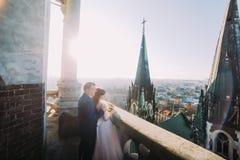 Nouveaux mariés heureux regardant sur la vieille vue étonnante de ville du balcon de la cathédrale gothique antique Photo libre de droits