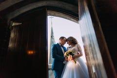 Nouveaux mariés heureux sur le balcon de la vieille cathédrale gothique Vue de porte Photo stock