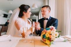 Nouveaux mariés heureux tenant des mains ensemble et rêvant de leur nouvelle vie mariée dans le restaurant à la table Photos stock