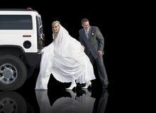 Nouveaux mariés poussant une limousine Image stock