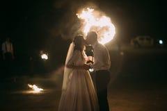 Nouveaux mariés romantiques embrassant la nuit devant le coeur flamboyant Photos libres de droits
