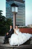 Nouveaux mariés s'asseyant à côté du réverbère Photographie stock libre de droits