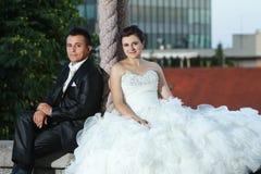Nouveaux mariés s'asseyant sur le mur Photos libres de droits