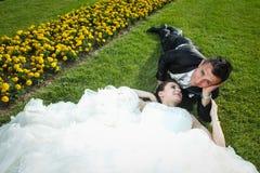 Nouveaux mariés se couchant sur la pelouse avec des fleurs Photos stock