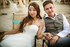 Nouveaux mariés se reposant sur la plage Photos libres de droits
