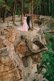 Nouveaux mariés se tenant au bord de la roche et des couples se regardant avec la tendresse et amour Mariée et marié Photographie stock