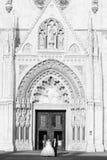 Nouveaux mariés se tenant devant la cathédrale noire et blanche Image stock