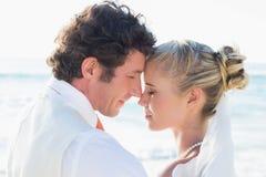 Nouveaux mariés se tenant prêt la mer face à face Images stock