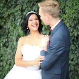 Nouveaux mariés sur le fond des feuilles vertes Images stock