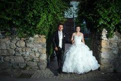 Nouveaux mariés tenant des mains et la marche Image stock