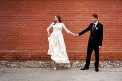 Nouveaux mari?s embrassant ? c?t? du mur de briques rouge Jeunes couples de mariage images stock