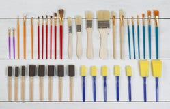 Nouveaux pinceaux et applicateurs organisés sur le conseil en bois blanc Photographie stock