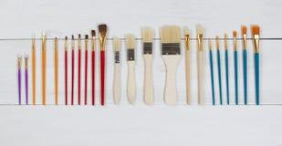Nouveaux pinceaux organisés sur les conseils en bois blancs Photo stock