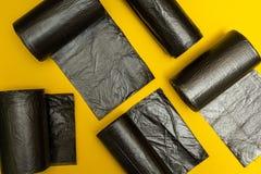 Nouveaux sacs de déchets noirs sur un fond jaune photos stock