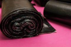 Nouveaux sacs de déchets noirs sur un fond rose photographie stock
