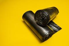 Nouveaux sacs de d?chets noirs sur un fond jaune images stock