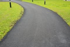 Nouvel asphalte qui est un passage couvert de route lisse dans le jardin d'herbe verte photographie stock