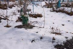 Nouvel enterrement avec une croix en bois et des fleurs artificielles, sur un vieux cimetière de village image libre de droits