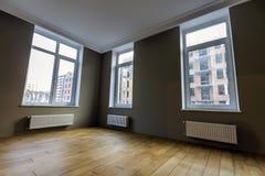 Nouvel intérieur rénové de pièce avec de grandes fenêtres, radiateurs de chauffage Images stock