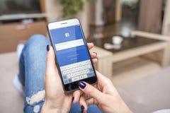 Nouvel iPhone noir 7 plus avec le réseau social Facebook dans des mains Photographie stock