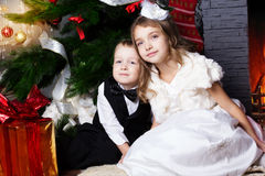 Nouvel an Les enfants heureux avec des cristmas se présente près du fourrure-arbre Photographie stock libre de droits