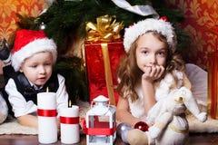 Nouvel an Les enfants heureux avec des cristmas se présente près du fourrure-arbre Photographie stock