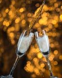 Nouvelle année à minuit avec des verres de champagne sur le fond clair Image libre de droits