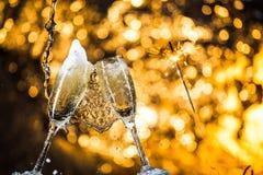 Nouvelle année à minuit avec des verres de champagne sur le fond clair Images libres de droits