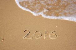 Nouvelle année 2016 écrite en plage sablonneuse l'image est rétro filtrée Photo stock