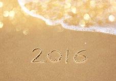 Nouvelle année 2016 écrite en plage sablonneuse l'image est rétro filtrée Images stock