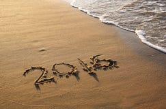 Nouvelle année 2016 écrite en plage sablonneuse l'image est rétro filtrée Image libre de droits