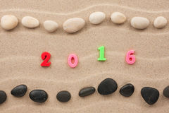 Nouvelle année 2016 écrite sur le sable parmi des pierres Images stock