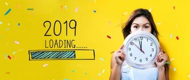 Nouvelle année de chargement 2019 avec la jeune femme tenant une horloge photographie stock