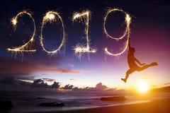 Nouvelle année 2019 l'homme sautant et dessinant sur la plage images stock