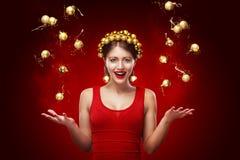 Nouvelle année, Noël, concept de vacances - femme de sourire dans la robe avec le boîte-cadeau au-dessus du fond de lumières 2017 Photos libres de droits