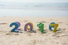 Nouvelle année 2017, texte coloré sur le sable de plage Photographie stock