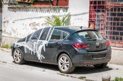 Nouvelle berline avec hayon arrière noire endommagée d'Opel Astra J garée sur la rue couverte et protégée avec le nylon au-dessus Image stock