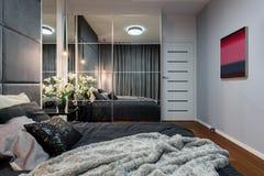 Nouvelle chambre à coucher avec la garde-robe reflétée photo stock