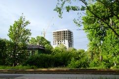 Nouvelle construction dans la ville et une vieille maison dans le premier plan Image stock
