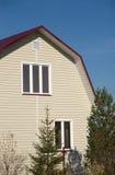 Nouvelle maison de campagne construite avec le toit rouge et couverte de voie de garage beige Photos stock