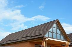 Nouvelle maison de construction avec de belles fenêtres de toit, lucarnes Construction de toiture Photographie stock libre de droits