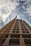 Nouvelle maison en construction avec une grue à tour contre le ciel bleu et les oiseaux dans le ciel Photographie stock libre de droits
