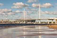 Nouvelle route de route avec le pont câble-resté au-dessus de la rivière de Neva dedans images stock
