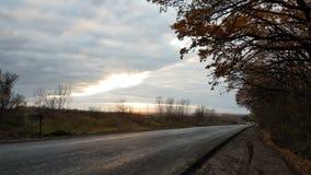 Nouvelle route pavée en collines d'automne au coucher du soleil banque de vidéos