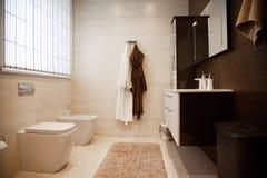 Nouvelle salle de bains lumineuse intérieure avec la promenade en verre dans la bordure de douche, armoire brune de vanité et app photographie stock
