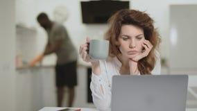 Nouvelles étonnées de lecture de femme blanche à l'ordinateur portable à la cuisine ouverte banque de vidéos